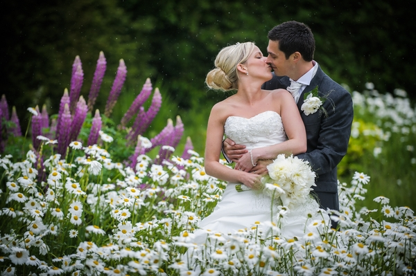 Bride and groom kissing in field of flowers - Picture by Pixies in the Cellar