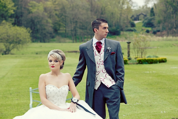 Groom standing next to bride sitting on chair - Gothic Wedding Photo Shoot at Browsholme Hall