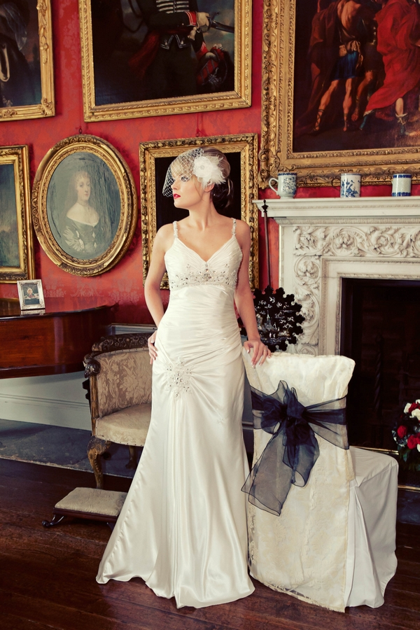 Bride posing by chair with chair cover - Gothic Wedding Photo Shoot at Browsholme Hall