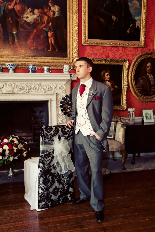 Groom posing by chair with black and white chair cover - Gothic Wedding Photo Shoot at Browsholme Hall