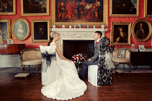 Bride and groom sitting on chairs by fireplace - Gothic Wedding Photo Shoot at Browsholme Hall