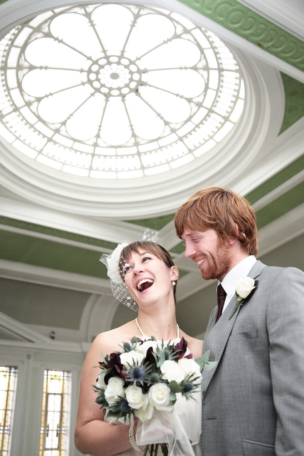 Bride smiling with groom under large skylight - Picture by Rebecca Prigmore Photography