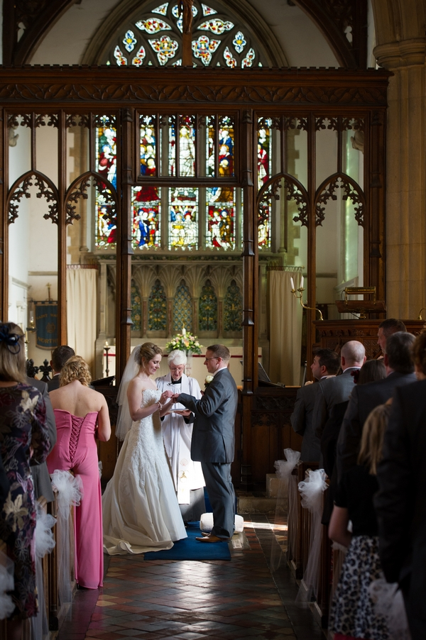 Bride and groom holding hands at altar - Picture by Gareth Squance Photography
