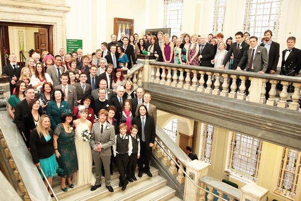 Wedding guests pose for group shot on balcony and staircase - Picture by Rebecca Prigmore Photography