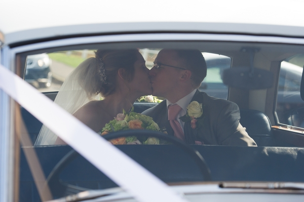Bride and groom kiss in back of wedding car - Picture by Gareth Squance Photography