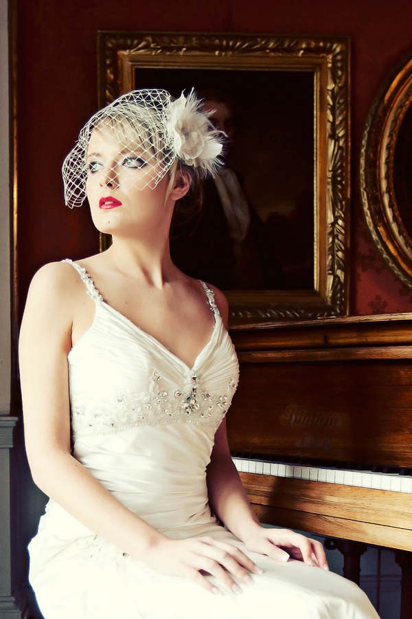 Bride with birdcage veil sitting by piano - Gothic Wedding Photo Shoot at Browsholme Hall