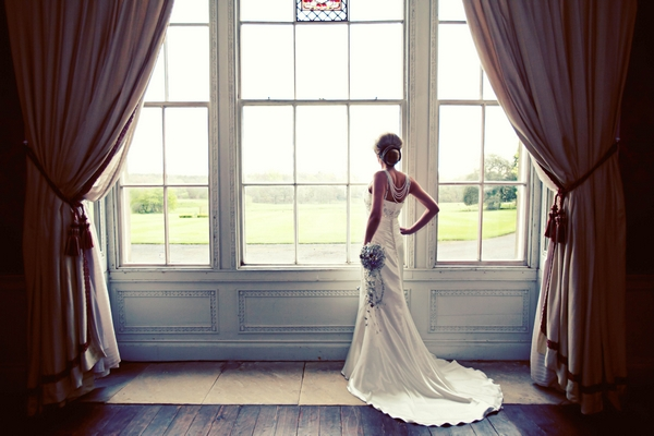 Bride standing by window - Gothic Wedding Photo Shoot at Browsholme Hall