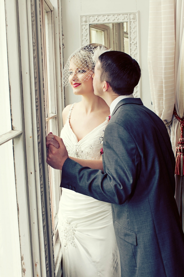 Groom kissing bride on cheek as she looks out of window - Gothic Wedding Photo Shoot at Browsholme Hall