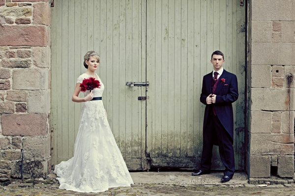 Bride and groom standing in front of green barn door - Gothic Wedding Photo Shoot at Browsholme Hall