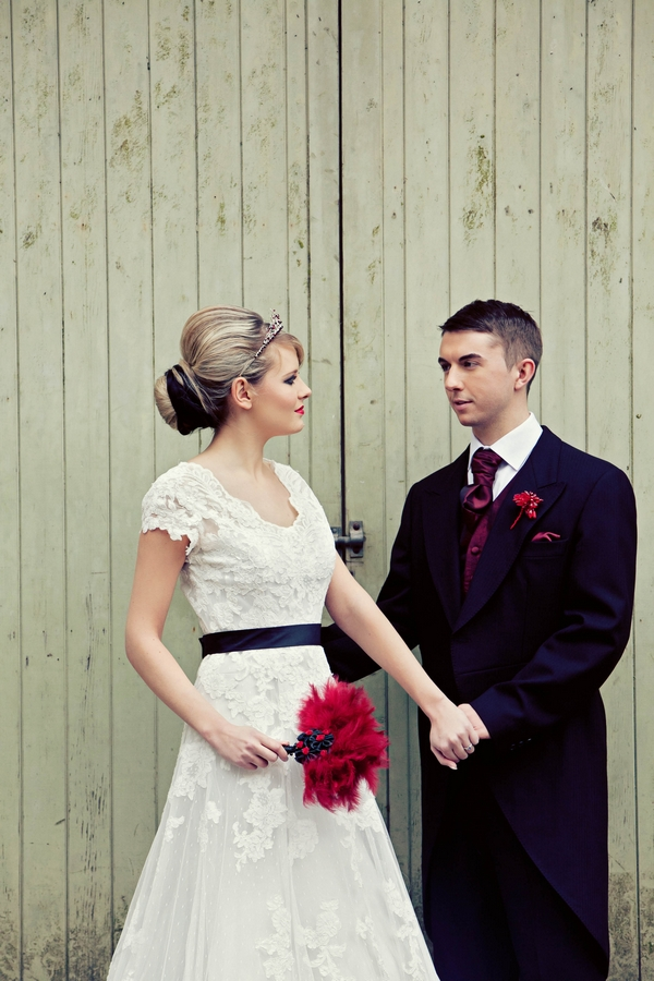 Bride and groom holding hands in front of barn door - Gothic Wedding Photo Shoot at Browsholme Hall