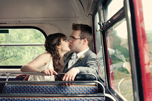 Bride and groom kiss in back of bus - A Homemade Marquee Wedding