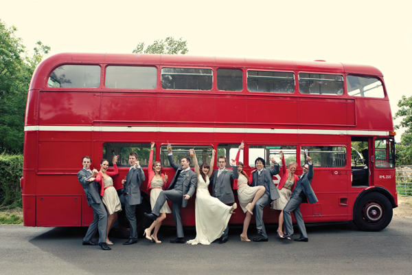 Wedding Party Posing For Photograph In Front Of Red Double Decker Bus