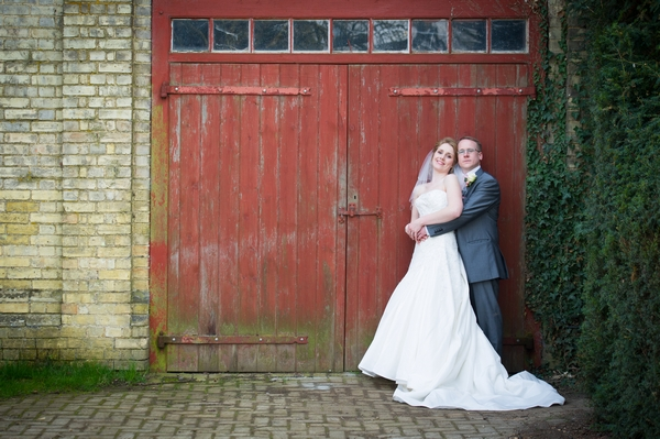 Bride and groom by red garage door - Picture by Gareth Squance Photography