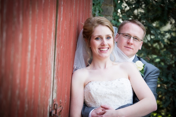 Bride and groom leaning on red door - Picture by Gareth Squance Photography