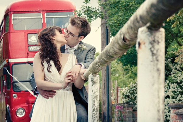 Bride and groom kiss by wooden rail - A Homemade Marquee Wedding