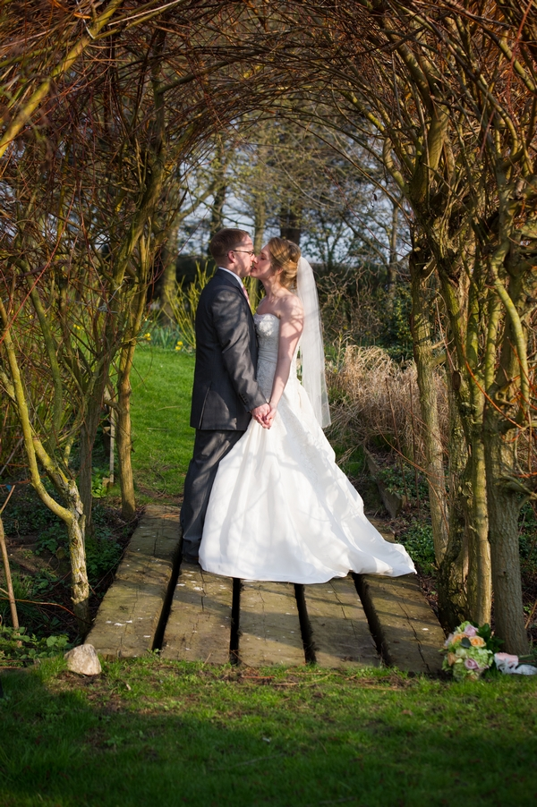 Bride and groom kissing on small wooden bridge - Picture by Gareth Squance Photography