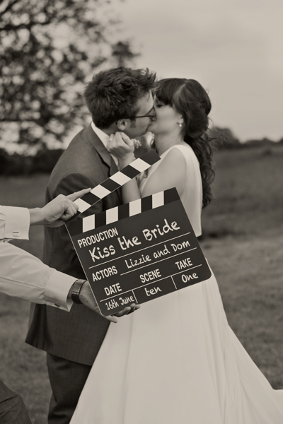Bride and groom kissing behind movie clapperboard - A Homemade Marquee Wedding