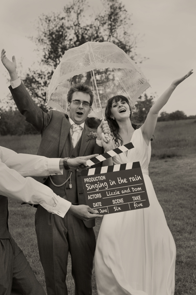 Bride and groom posing with umbrella behind movie clapperboard - A Homemade Marquee Wedding