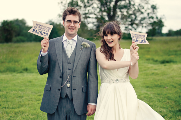 Bride and groom holding Just Married flags - A Homemade Marquee Wedding