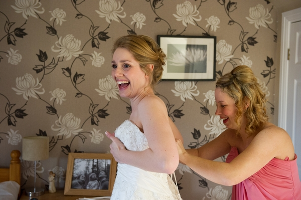 Bride laughing as her dress is fastened - Picture by Gareth Squance Photography