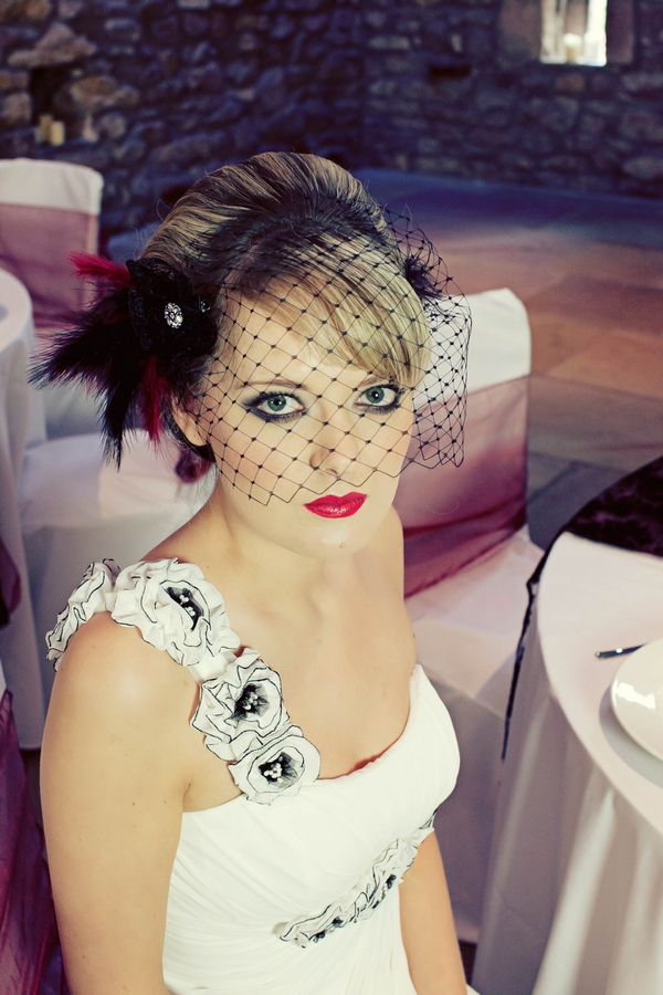 Bride wearing birdcage veil siitng on chair - Gothic Wedding Photo Shoot at Browsholme Hall