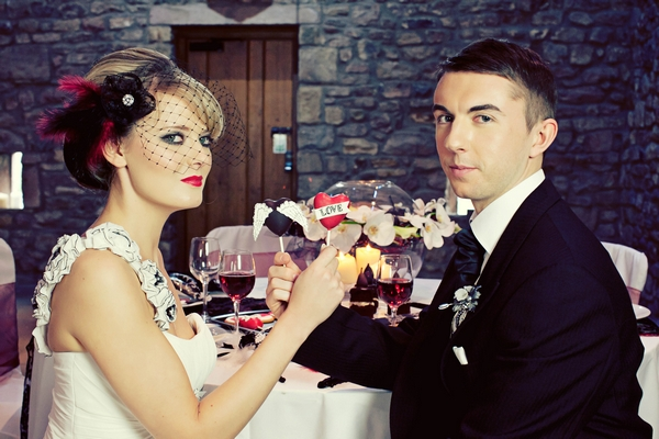 Bride and groom holding cake pops - Gothic Wedding Photo Shoot at Browsholme Hall