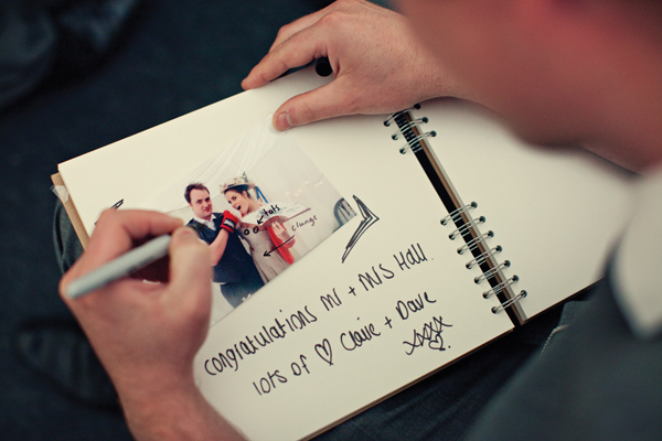 Guest writing message in guest book - A Homemade Marquee Wedding