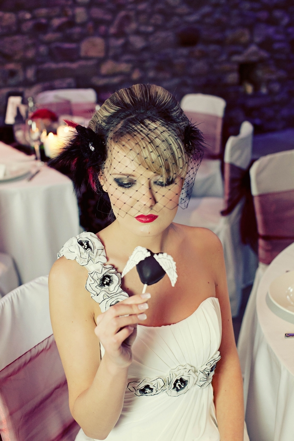Bride holding cake pop - Gothic Wedding Photo Shoot at Browsholme Hall