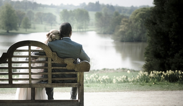 Bride and groom sitting on a bench looking at a lake - Picture by Little Jewel Photography