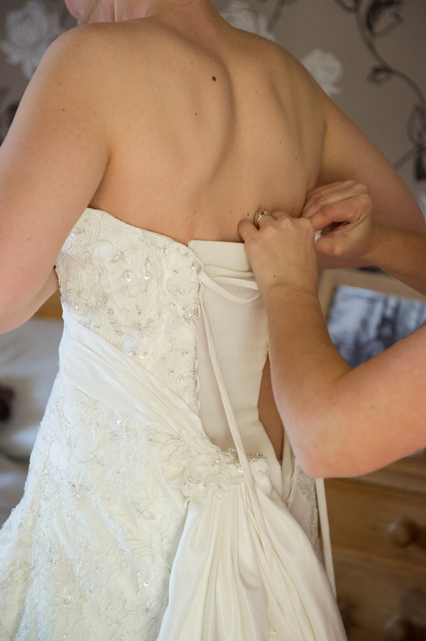 Back of wedding dress being fastened - Picture by Gareth Squance Photography