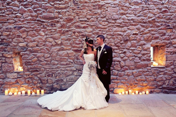 Gothic bride and groom standing in front of wall of barn - Gothic Wedding Photo Shoot at Browsholme Hall