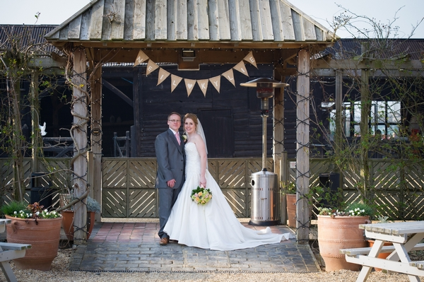 Bride and groom standing under bunting - Picture by Gareth Squance Photography