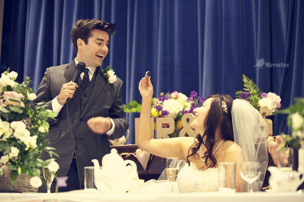 Groom smiling at bride during wedding speech - Picture by Mirrorbox Photography
