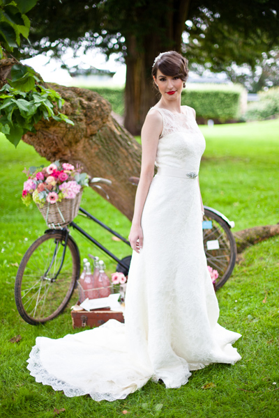 Model wearing wedding dress, standing in front of bicycle - LoveLuxe Launch