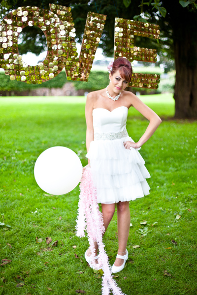 Model wearing wedding dress holding balloon - LoveLuxe Launch