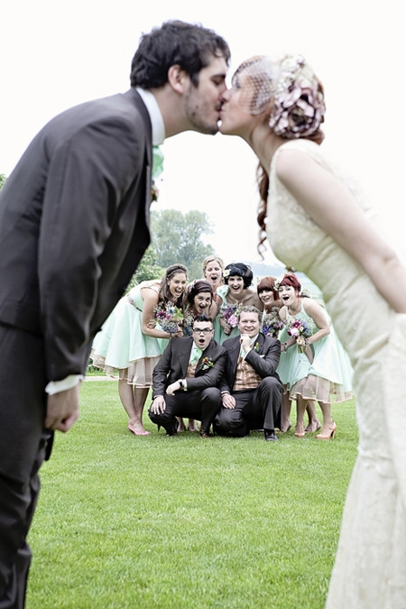 Wedding party watching bride and groom kiss - Picture by Oscar and Rose Photography