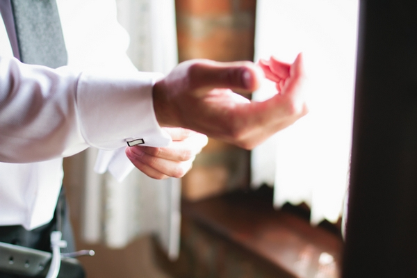 Groom fastening cufflink - A Spring Themed Wedding in Hungary
