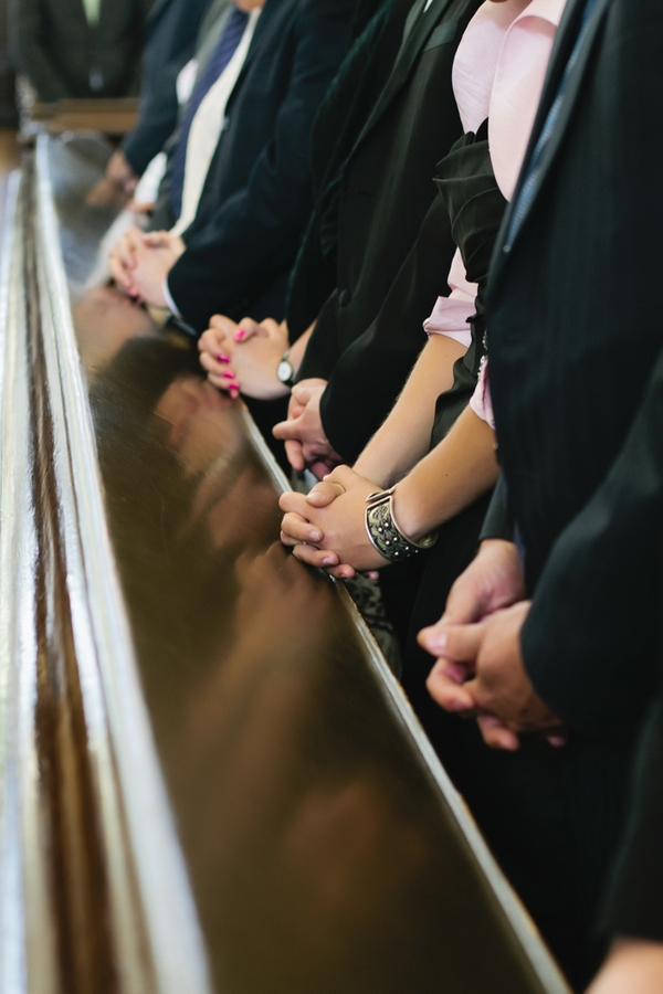 Hands clasped in church - A Spring Themed Wedding in Hungary