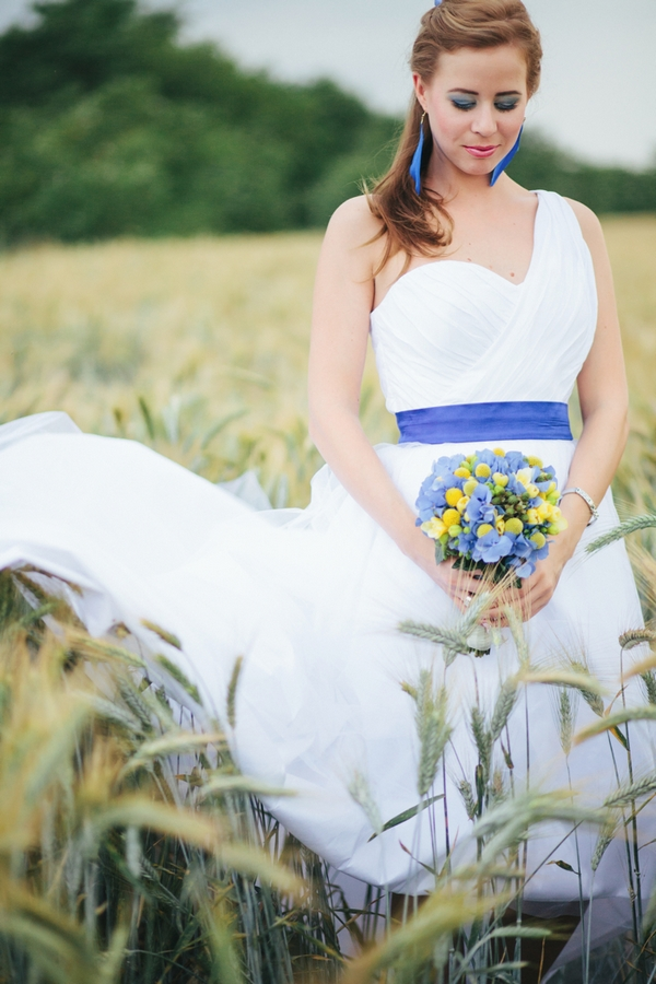 Bride standing in corn field - A Spring Themed Wedding in Hungary