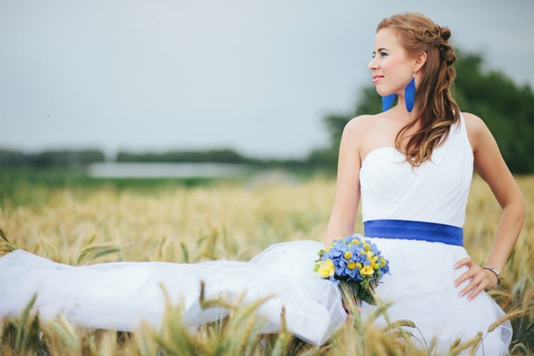 Bride with hand on hip in corn field - A Spring Themed Wedding in Hungary