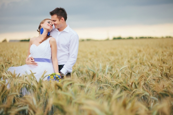 Bride and groom posing in corn field - A Spring Themed Wedding in Hungary