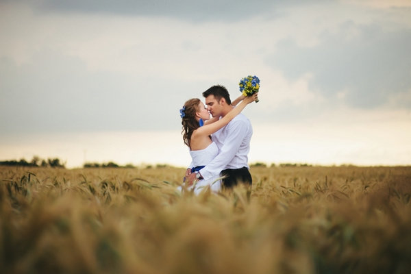 Bride with arms around groom in corn field - A Spring Themed Wedding in Hungary