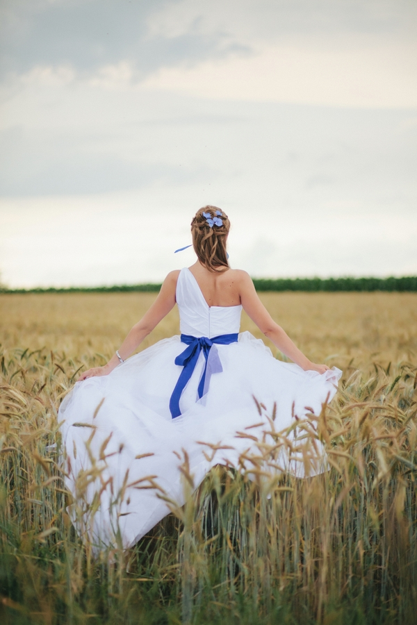 Back of bride walking through corn field - A Spring Themed Wedding in Hungary
