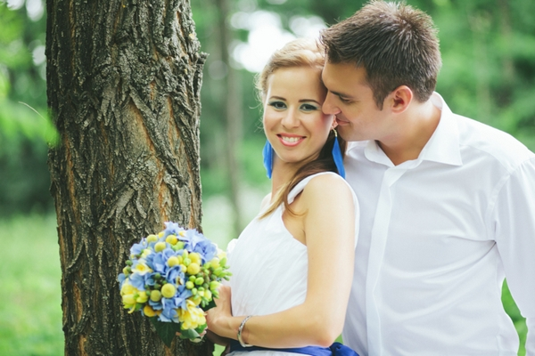 Bride and groom standing by tree - A Spring Themed Wedding in Hungary