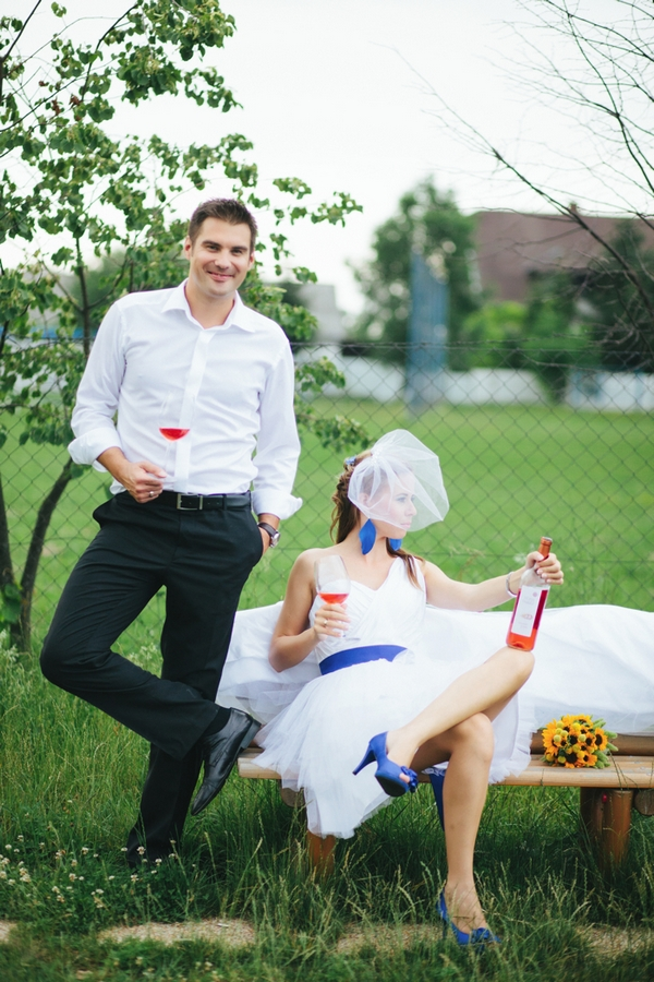 Bride and groom drinking wine on bench - A Spring Themed Wedding in Hungary