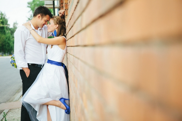Bride and groom leaning on wall - A Spring Themed Wedding in Hungary
