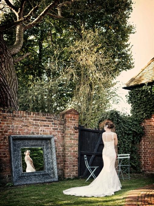 Bride looking in mirror in garden - Picture by Jasmine Jade Photography