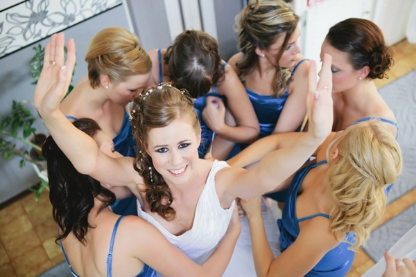 Bridesmaids helping bride put on dress - A Spring Themed Wedding in Hungary