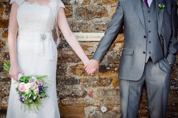 Bride and groom holding hands in front of sign - Picture by Aaron Collett Photography