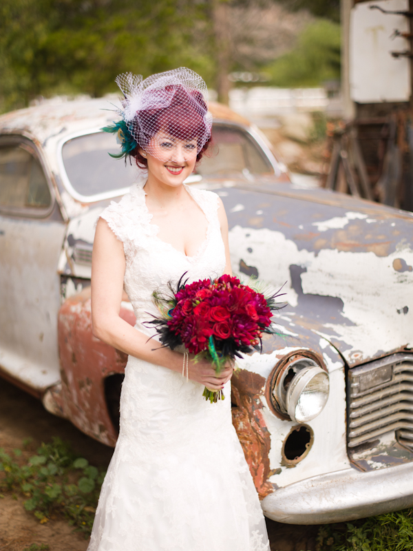 Bride standing in front of old car